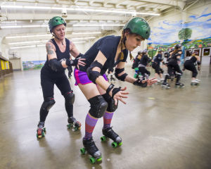 """Reporter Skates After Her Derby Girl Dreams : """"Malice,"""" left, of the Port City Roller Girls roller derby team, slowly pushes News-Sentinel reporter Sara Jane Pohlman to teach her proper skating technique at the San Joaquin County Fairgrounds on Thursday, Feb. 7, 2013.  - Dan Evans/News-Sentinel"""