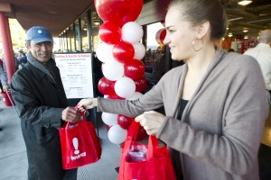 """BevMo! Opens In Lodi: James Takahashi, left, of Elk Grove is handed a gift bag by Christina Schultz as he enters BevMo! on Kettleman Lane in Lodi on Friday, Nov. 9, 2012. Takahashi, the first customer in line, arrived at the sore at 5 a.m. BevMo! opened Friday morning with hundreds of people waiting in line to get a glimpse of the new store on Kettleman Lane near Walmart and Food-4-Less. The store gave out gift bags worth $50 to the first 500 customers and welcomed the customers into the store. The store features more than 1,500 wines, including local varietals, 1,700 beers and 1,700 spirits along with gourmet food items, cocktail mixers and bar accessories. The store will have special tastings and events all weekend to celebrate their opening. Below is a glimpse into the BevMo! opening: The first in line Starting at 5 a.m., James Takahashi was in line at the Lodi BevMo! location with his newspaper and a small collapsible chair. Having been at the Stockton BevMo! grand opening more than 6 years ago, Takahashi knows what it takes to wait for hours for one of his favorite stores. He was most excited about Michael~David wines at the store. """"I wanted to check out the selection they have, and I know local winemakers are pouring,"""" he said. The district manager As the line for BevMo! wrapped around the block, district manager Jill Doe said she had no worries that people would show up for the grand opening. """"We call them BevMo! fans. Rain, snow, sleet or hail, they're coming out,"""" Doe said. This is the fourth store Doe has opened this year, and she will be opening up a location in Santa Monica next week. She stressed that everyone will find something they enjoy at the new store. """"We have something for every palette, from the beginner drinker to the more experienced,"""" Doe said. Because people often buy beer, wine and spirits when they are having a baby, getting married or other life celebrations, Doe said the employees becomes a part of their customers' lives. """"We are your n"""