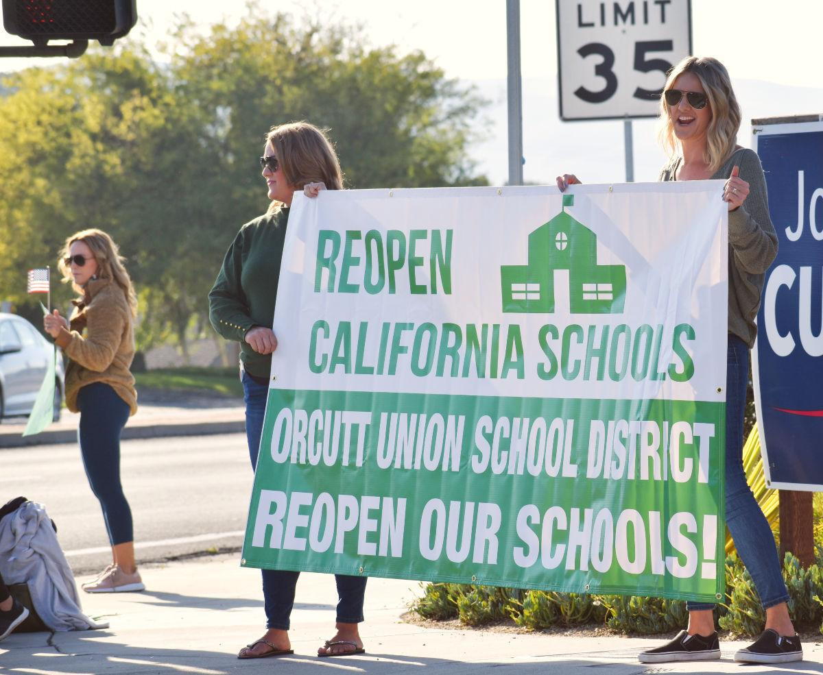 Parents from the Orcutt Union School District rally with signs to open schools at the corner of Clark and Bradley Wednesday