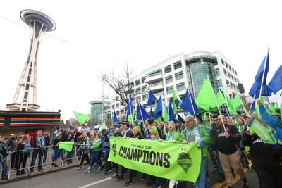 Fans show their support for the Seattle Sounders during the team's MLS Cup victory parade on November 12, 2019, in Seattle.