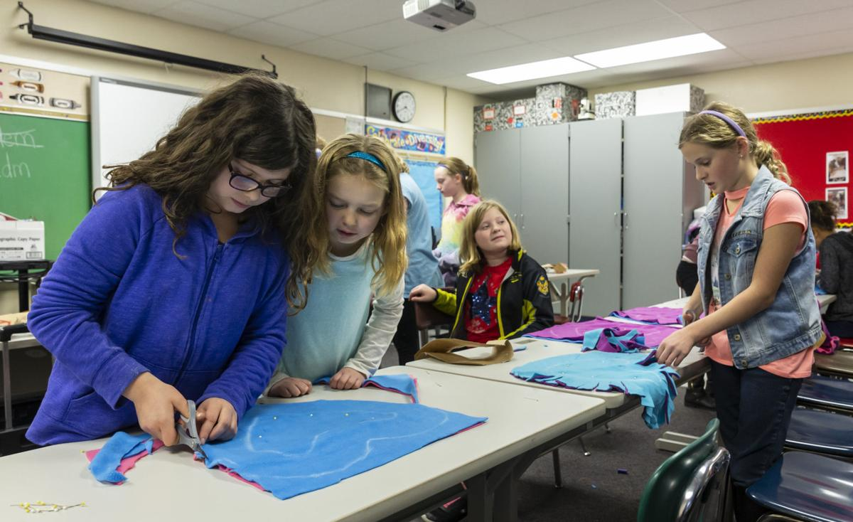 Students cut fabric for charity