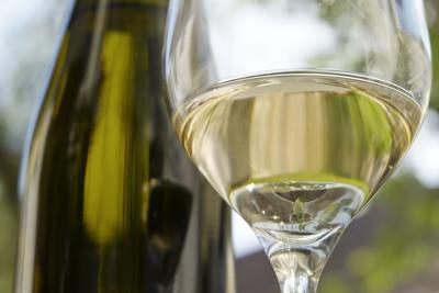 Wine glass with white wine in front of a bottle - Wachau - Austria
