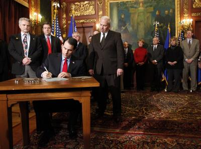 Gov. Scott Walker signs his signature collective bargaining law known as Act 10