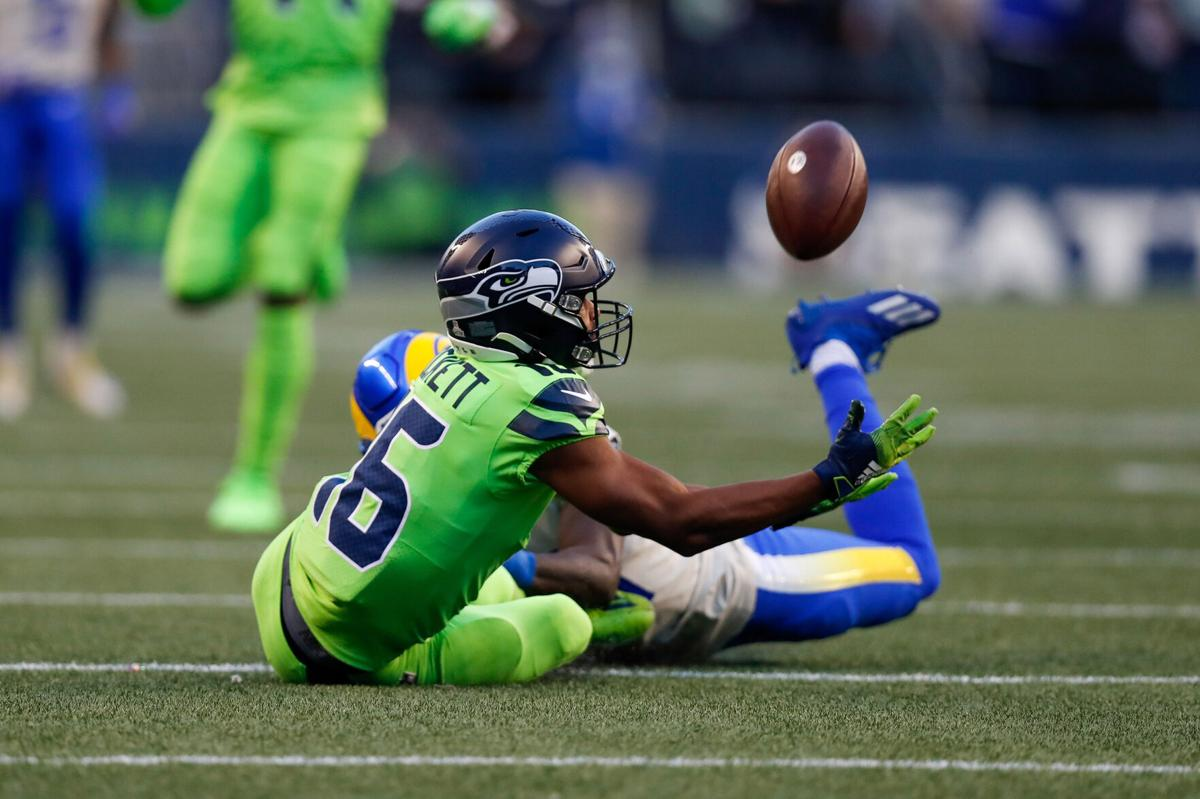 Seattle Seahawks wide receiver Tyler Lockett almost comes down with pass after being dragged to the ground by Los Angeles Rams cornerback Robert Rochell, who was flagged for a pass interference penalty during the second quarter on Thursday, Oct. 7, 2021, at Lumen Field in Seattle.
