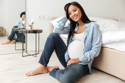 Happy pregnant asian woman leaning on a sofa while sitting