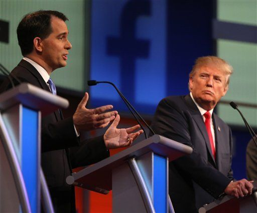 Scott Walker speaks while Donald Trump looks on