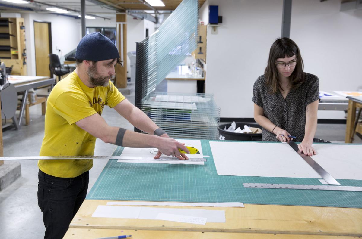Jason Ruhl, left, and Elizabeth Younce cutting paper
