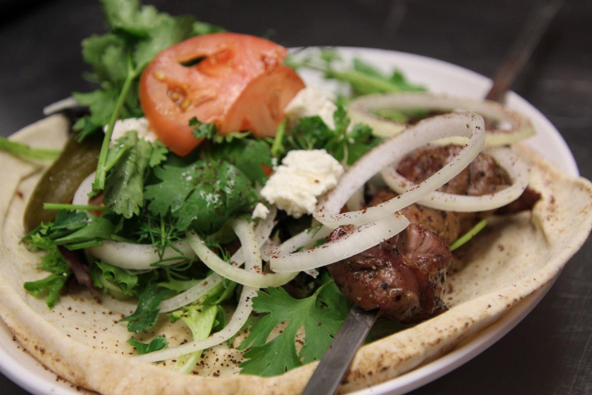 Cooked lamb kabob on toasted pita bread with parsley, tomato, goat cheese, onions and pickles sprinkled with chili powder .JPG