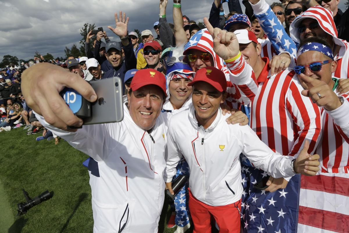 Phil Mickelson, Rickie Fowler selfie with fans, AP photo, Presidents Cup