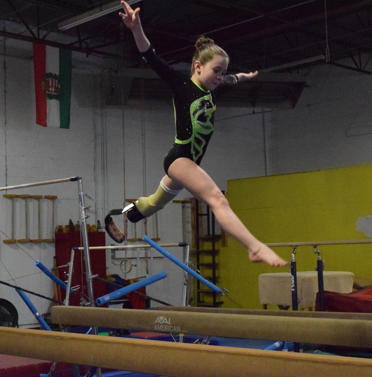 Zoe Smith, 10, performs on the balance beam. Zoe competes with a prosthetic left leg due to her left foot being amputated at age one.