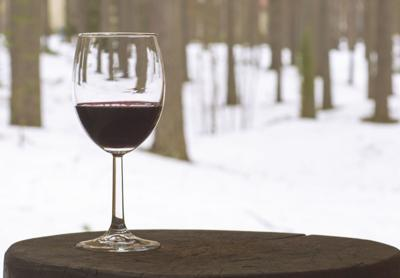Red wine in glass goblet on a background of trees.