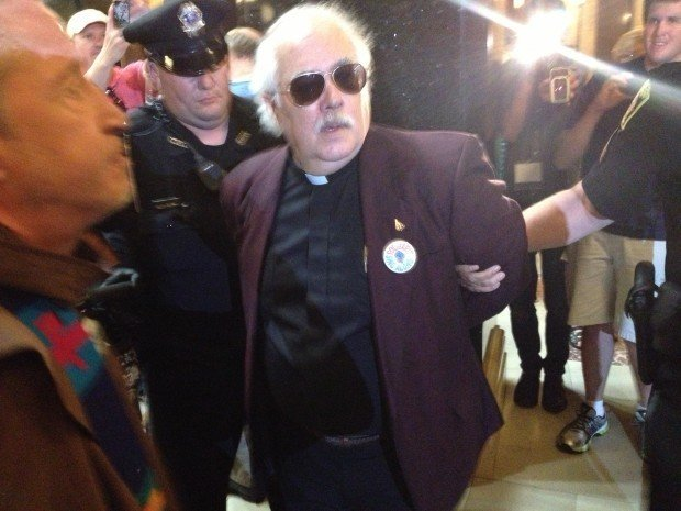 The Rev. Carter Dary is arrested Friday at the Solidarity Singalong