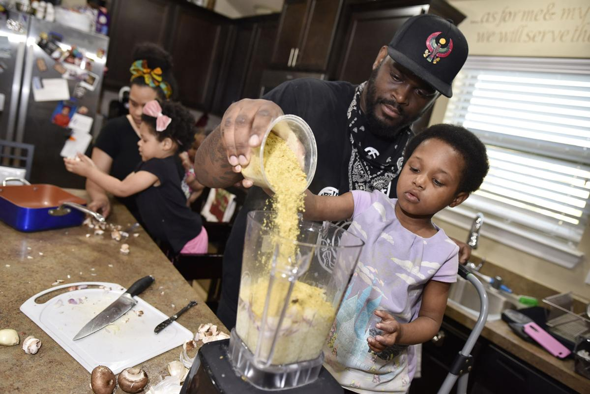 Captain McGee, 4, right, helps her father pour ingredients into a blender for a vegan pasta at their home in DeSoto on Tuesday afternoon, April 9, 2019. McGee's daughter Captain has a lot of food allergies and eating vegan meals helps tremendously with that.