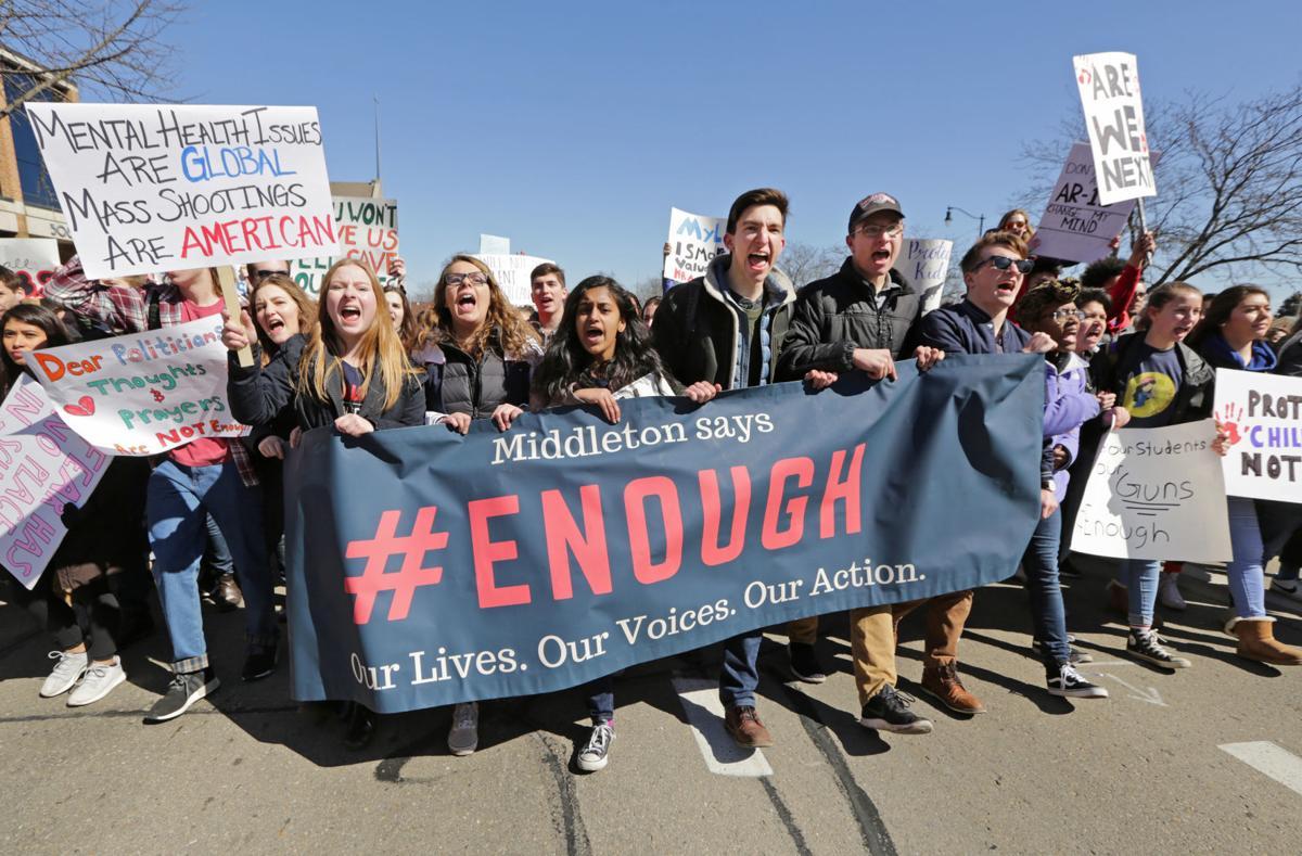 Students carry banner demanding stricter gun laws