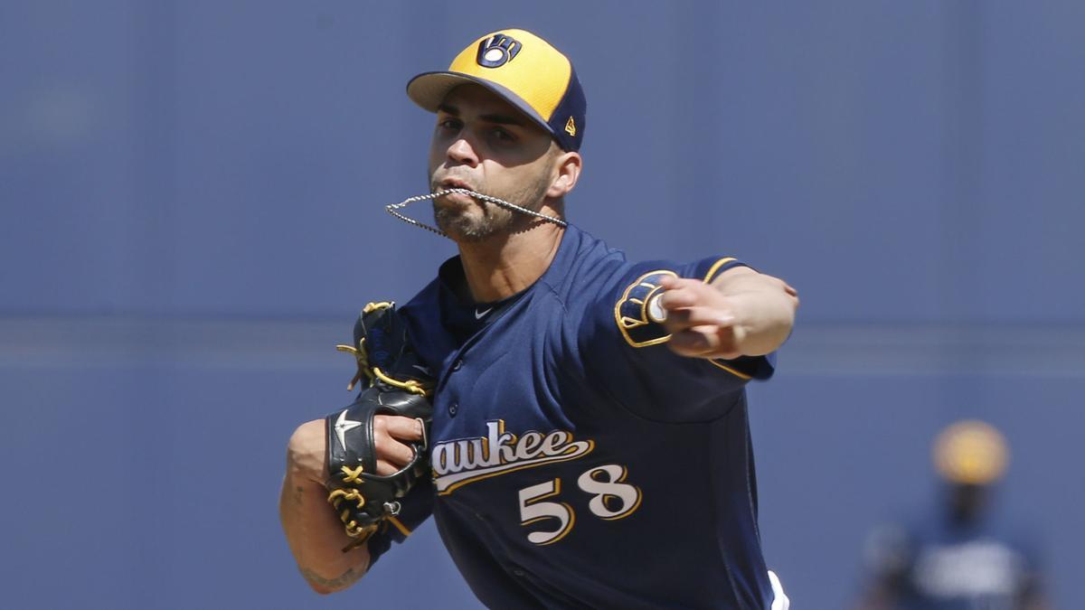 Alex Claudio pitches, AP
