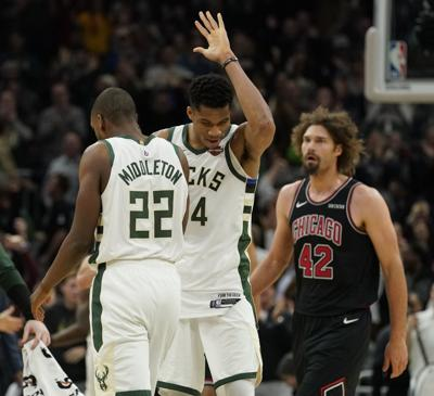 7b35ff5b4f6 bucks photo 11-29. Bucks  Khris Middleton is congratulated by Giannis  Antetokounmpo after making the ...