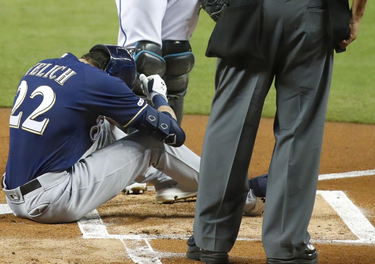 Christian Yelich on ground after fracturing kneecap, AP photo