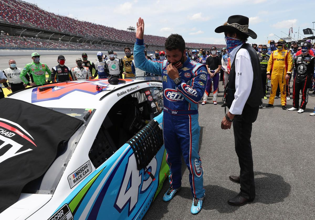 Bubba Wallace, driver of the #43 Victory Junction Chevrolet, and NASCAR Hall of Famer and team owner Richard Petty look on after NASCAR drivers pushed Wallace to the front of the grid as a sign of solidarity with the driver prior to the NASCAR Cup Series GEICO 500 at Talladega Superspeedway on June 22, 2020 in Talladega, Ala. A noose was found in the garage stall of NASCAR driver Bubba Wallace at Talladega Superspeedway a week after the organization banned the Confederate flag at its facilities.