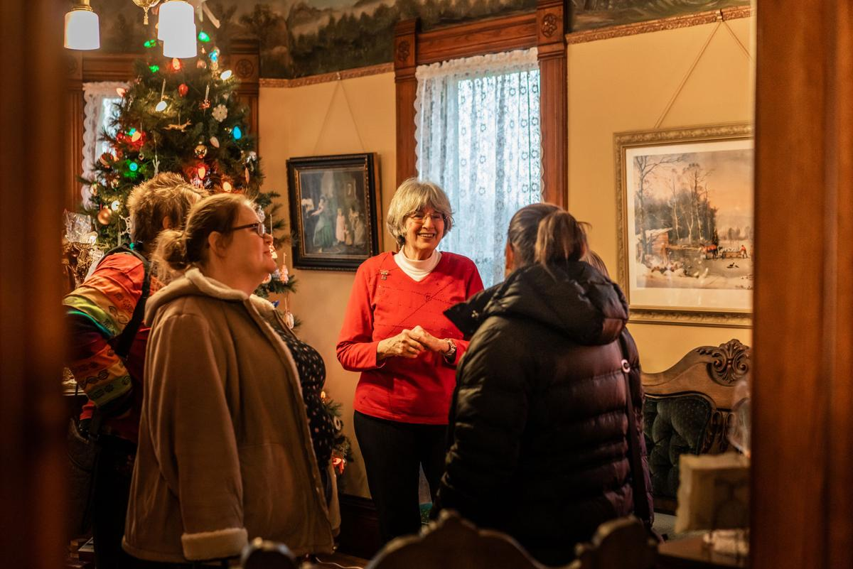Tour guide with guests at the Larson House Museum