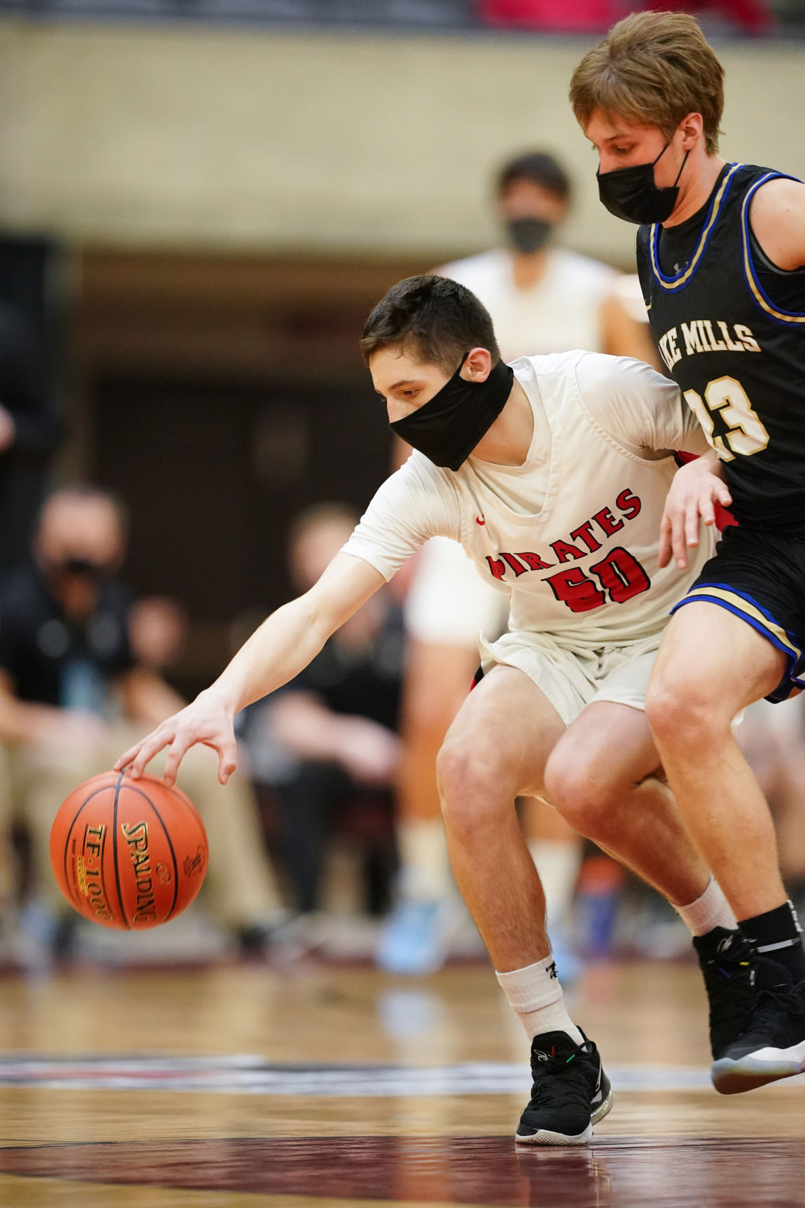 WIAA boys basketball photo: Lake Mills Charlie Bender tries to bump the ball away from Pewaukee's Nick Janowski