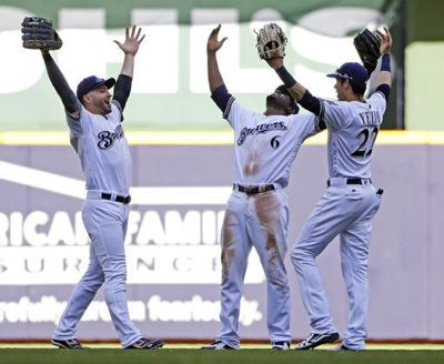 Ryan Braun, Lorenzo Cain, Christian Yelich celebrate, AP photo