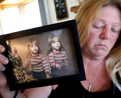 Sherri holding photo of sons