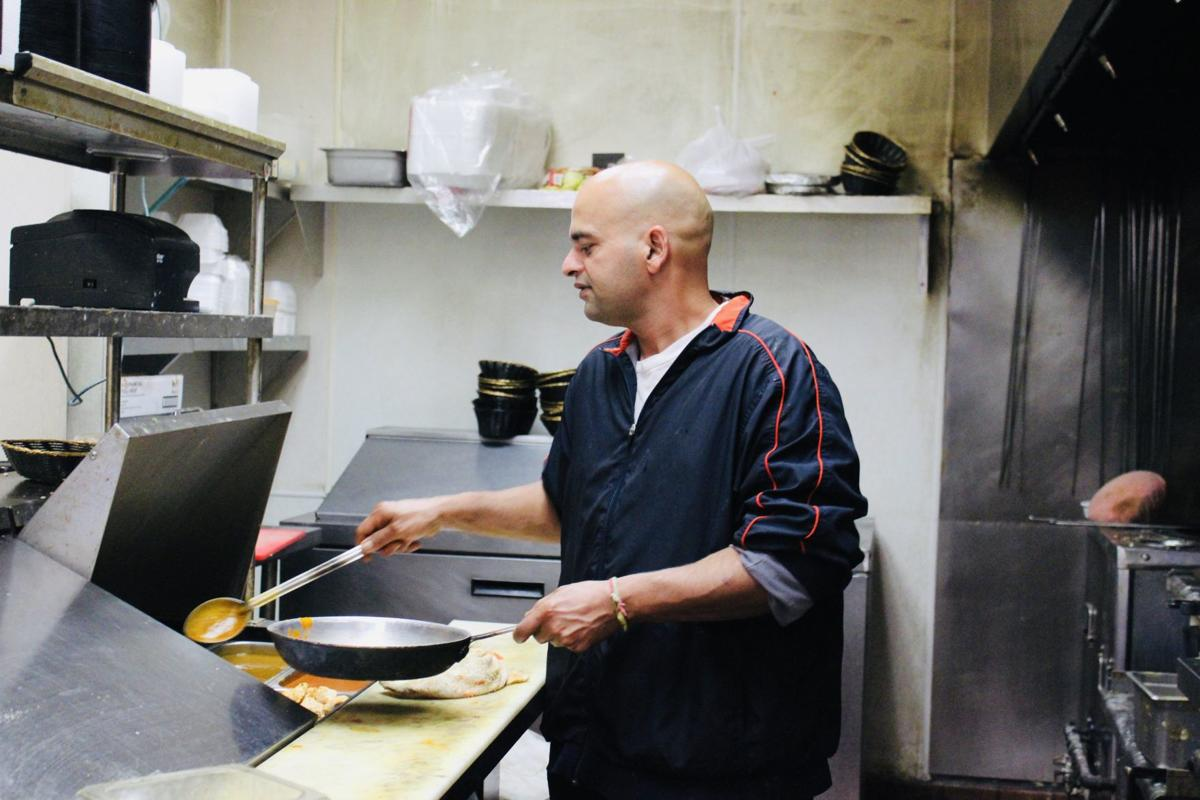 Shavinder Singh (co-owner and chef) cooking with curry in Royal Indian's back kitchen.jpeg