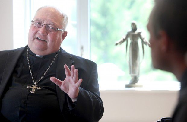 Bishop Morlino meets with staff in July of 2013