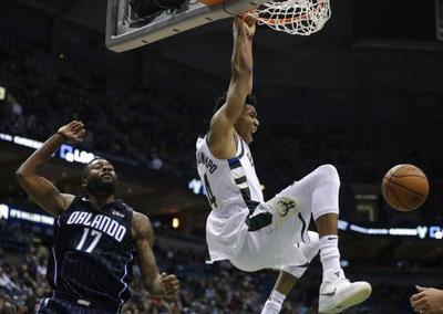Giannis Antetokounmpo hangs on rim, AP photo