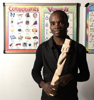 Amisi Juma Holds Carving Above All Else