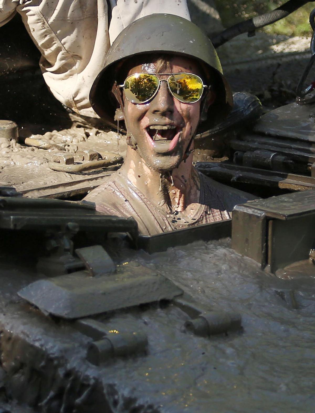 Reporter Patrick Connolly gets a face full of muddy water as he drives a tank at Tank America in Melbourne, Fla., on June 27, 2019.