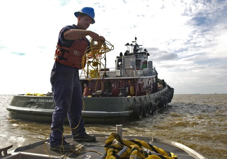 A member of the U.S. Coast Guard pulls in a tugboat