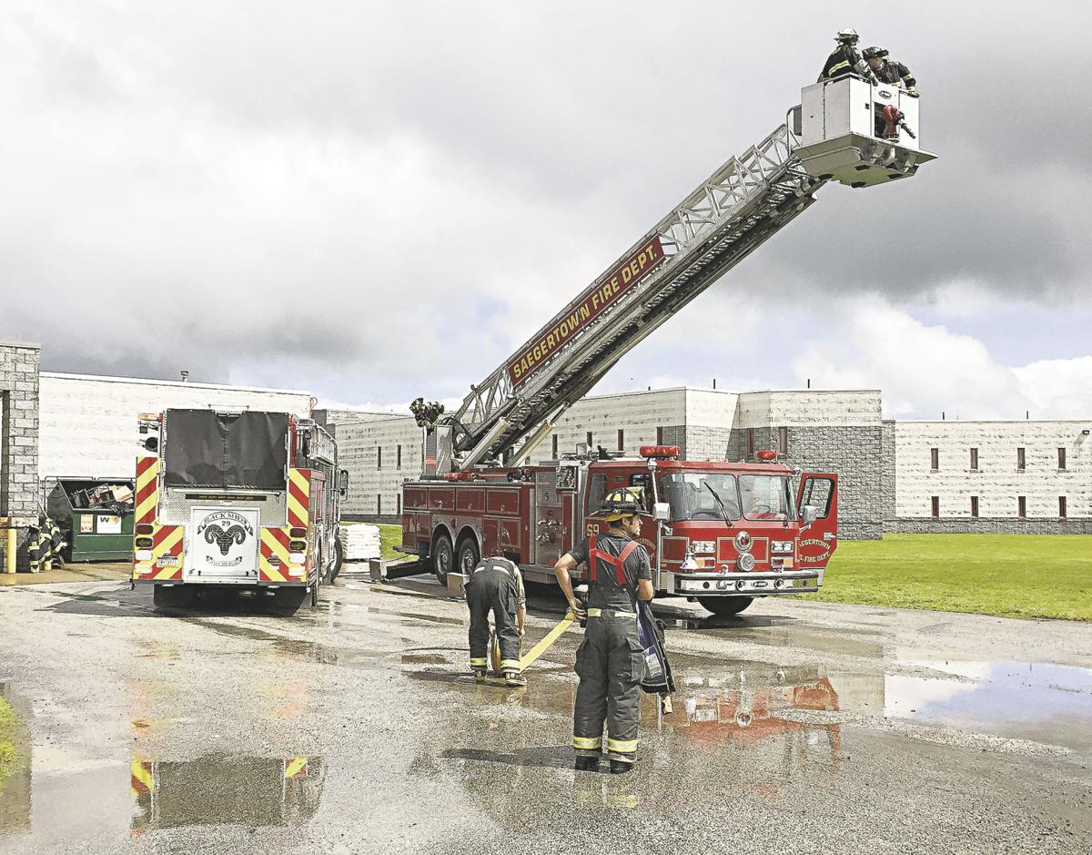 Firemen pack up hoses and other equipment in the wake of a dryer fire in the laundry room at the crawford county jail in saegertown on thursday