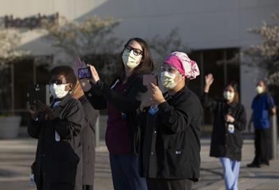 Health care workers wave and watch community members parade past the front of M Health Fairview Ridges Hospital last month in Burnsville. Christine T. Nguyen | MPR News file