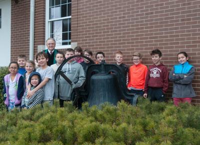 Historic bell, pastor and children