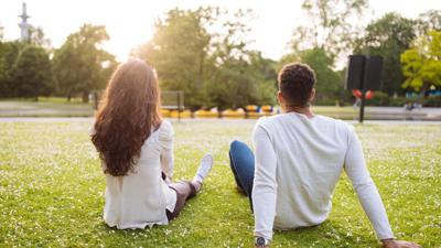 young-couple-sitting-in-park-g667612289.jpg