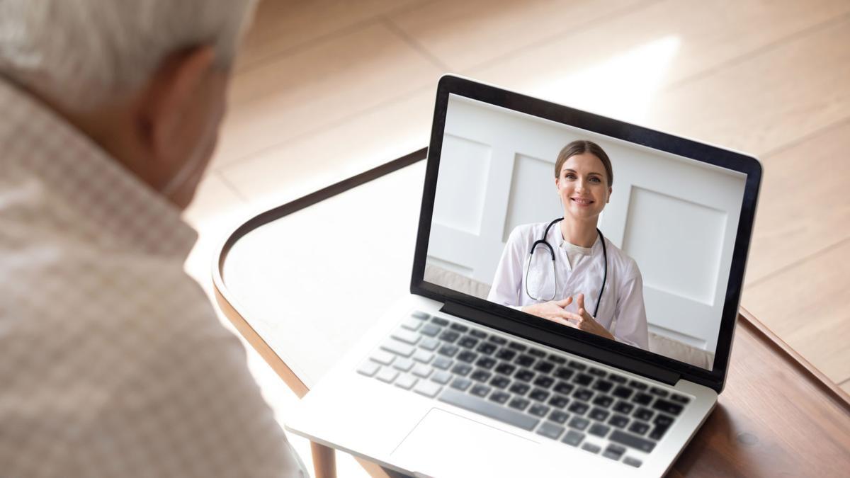Elderly man having online video consultation with doctor