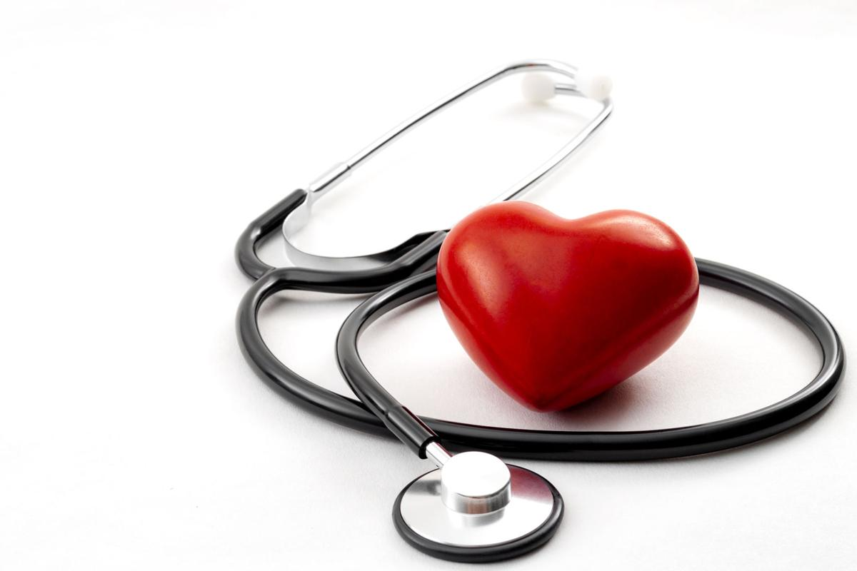 Yearly health check up, disease diagnosis medicine, healthcare and cardiology concept with a red heart and a stethoscope isolated on a hospital white background