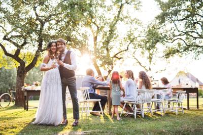 Bride and groom clinking glasses at wedding reception outside in the backyard.