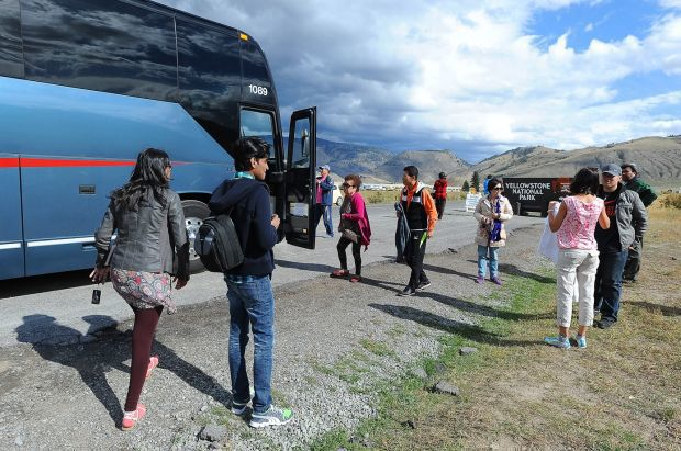 Tourists from China and India stand outside their tour bus