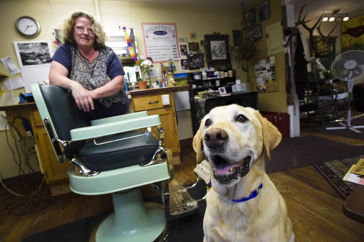 Dundee Warden, owner of Dundee's Barber Shop, and Charlie pose for a photograph