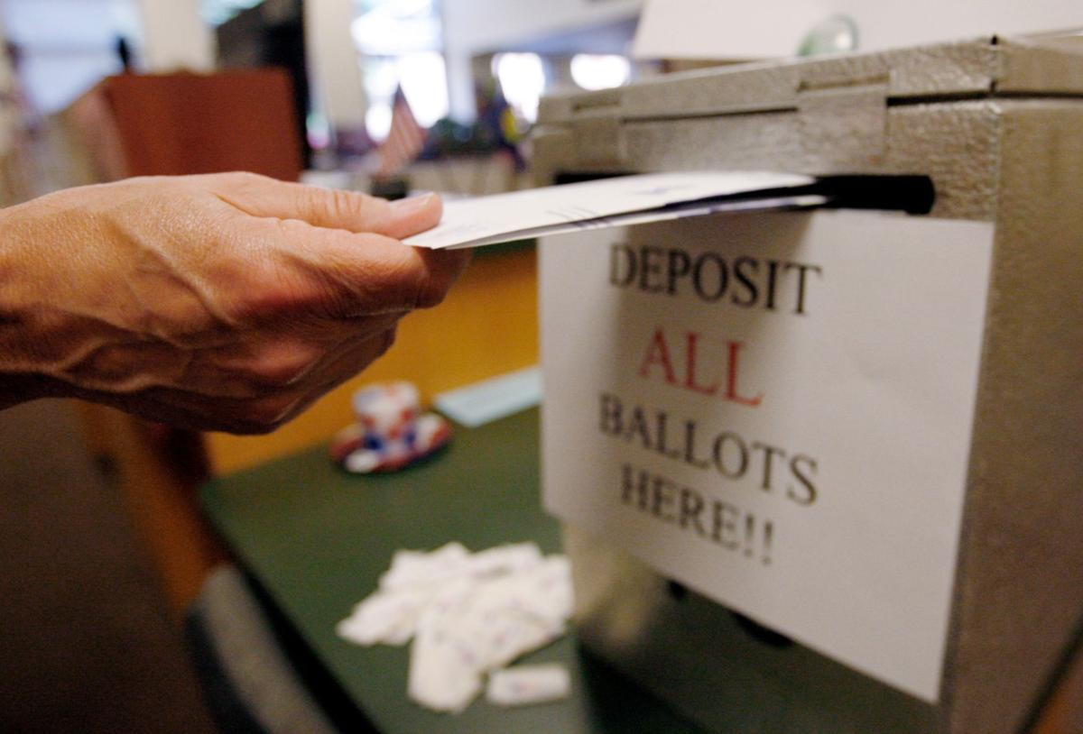 A voter drops their ballot off