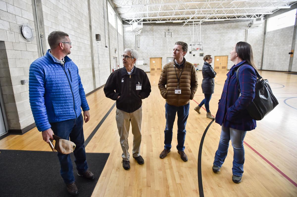 Lt. Gov. Mike Cooney and Chief Deputy Attorney General Jon Bennion, center, receive a tour of the former Montana Developmental Center