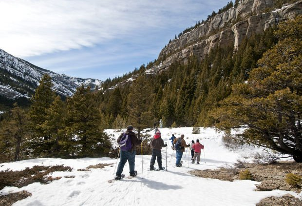 Hikers on snowshoes walk through the Devil's Glen