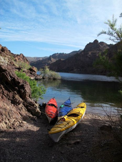 Kayaks sit on the shore of the Colorado River