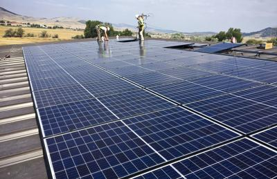 Crews members of Solar Montana install a solar panel array