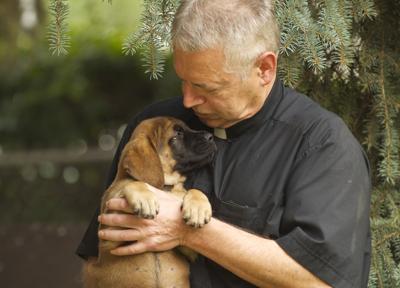 Father Patrick Beretta, puppy nuzzle