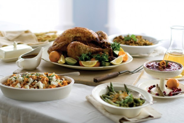 A citrus turkey is surrounded by sweet potatoes