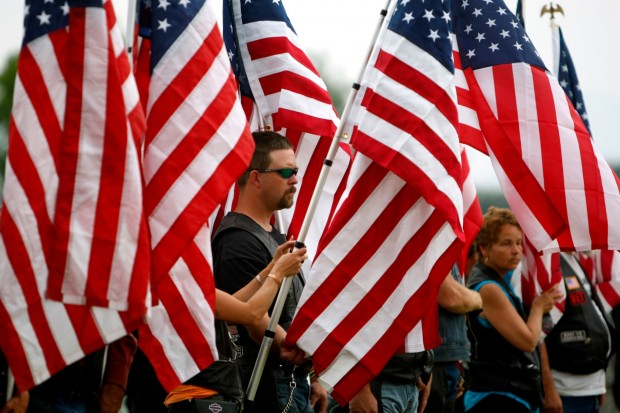 People hold flags during an interment ceremony