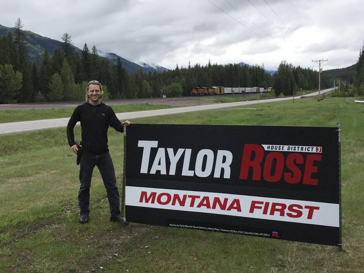 Taylor Rose poses with a campaign sign of his from the 2016 race for House District 3